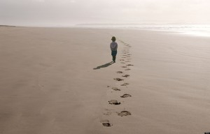 Young girl walking along a beach following footsteps
